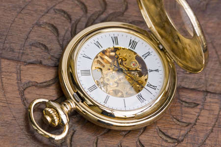 Close up of a gold pocket watch on wooden surface photo
