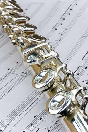dwarsfluit: Fluit lag schuin tegenover bladmuziek notities Stockfoto