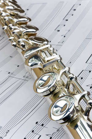 flute instrument: Flute lay diagonally across sheet music notes
