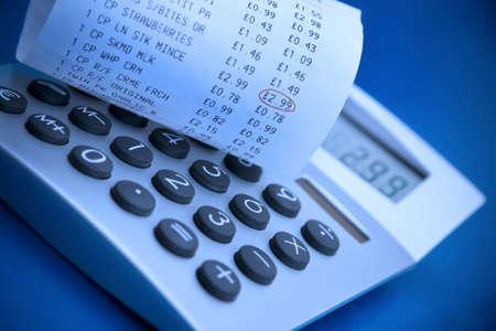 Checking supermarket cash register receipt with calculator photo