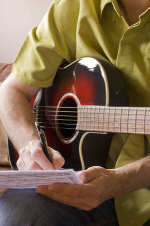 Songwriting on a red sunburst acoustic guitar Stock Photo