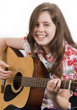 ni�o cantando: Sonriente ni�a rasgueando una guitarra ac�stica aislada en blanco