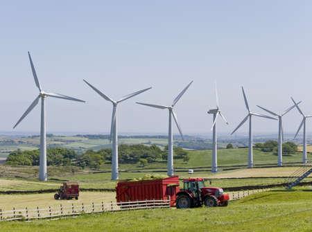windfarm: Molinos de viento en WindFarm con los tractores que trabajan en primer plano  Foto de archivo