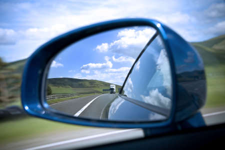Rear view mirror reflecting road and sky