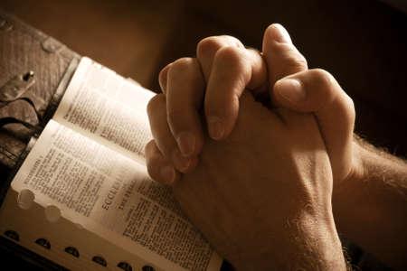 bible ouverte: Poings ferm�s dans la pri�re sur une bible ouverte Banque d'images