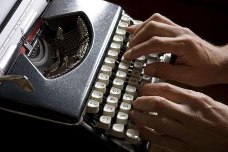 typebar: Man typing on an old portable typewriter