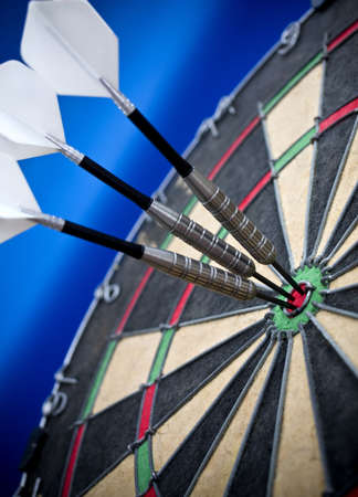Three darts in the bulls eye Stock Photo