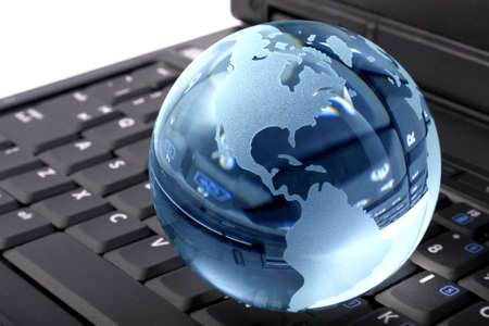 Blue glass globe on a laptop keyboard photo