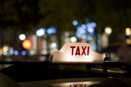 fare: Taxi waiting for a fare in the city with its sign illuminated Stock Photo