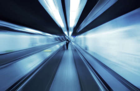 elevated walkway: Motion blurred people travelling on a travolator walkway late at night Stock Photo