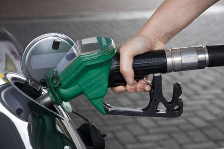 fuel tank: Hand holding green fuel pump refuelling a car