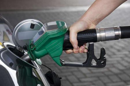 station service: Une main tenant la pompe de ravitaillement en carburant �cologique d'une voiture