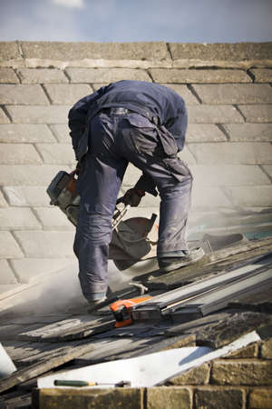 Roofer cutting roof tiles with circular saw photo
