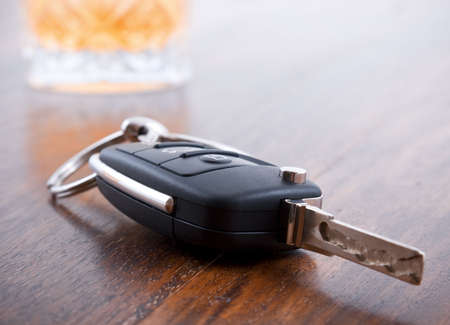 Drunk driving concept - car keys in the foreground with glass of whiskey photo