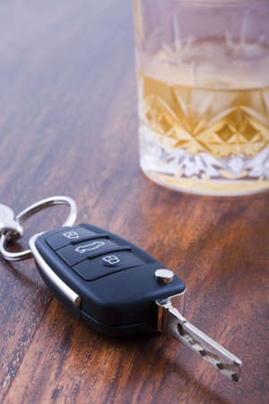 impairment: Drunk driving concept - car keys on table with glass of whiskey