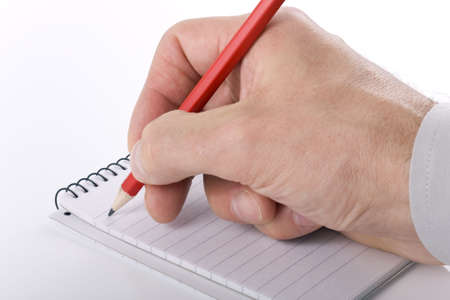 Close up of businessman taking notes in spiral notebook photo