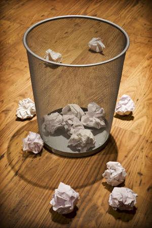 waste paper: Chatarra documento sobre piso de madera alrededor de papelera