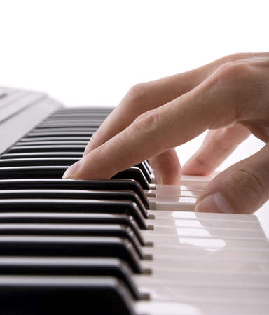 backlit keyboard: A musicians hand on a keyboard isolated on white