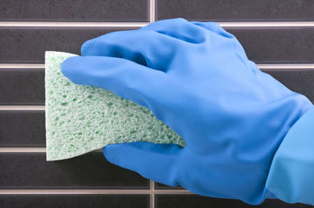 scrubbing up: Hand in rubber glove scrubbing bathroom tile with a sponge