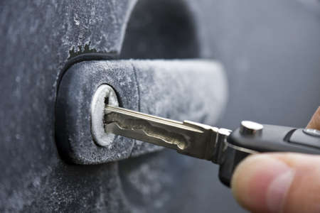 Unlocking a car door on a cold frozen winter morning