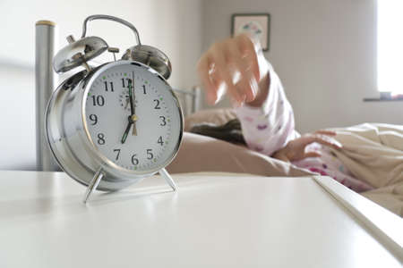 exaggerate: Young woman turning off alarm clock, motion blur on hand to exaggerate action, white copy space beneath