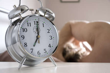 Alarm clock on bedside table with man sleeping in bed