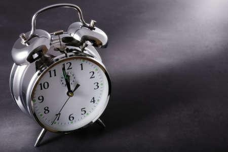 despertador: Alarma por la noche justo antes de la medianoche sobre un fondo oscuro Foto de archivo