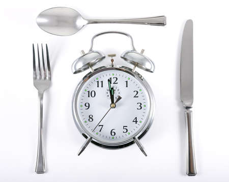 Alarm clock with knife fork and spoon for mealtime concept photo