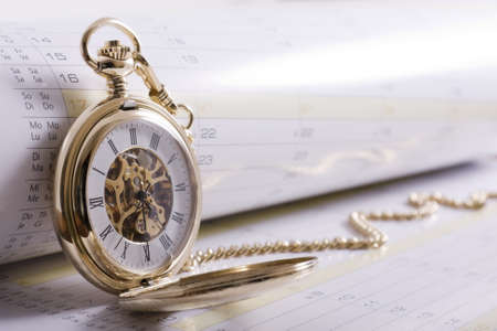 Business scheduling concept - high key shot of gold pocket watch on calendar with copy space photo