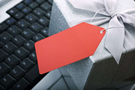 wrapped present: E commerce or business gift concept - Gift wrapped present with blank red tag on laptop keyboard