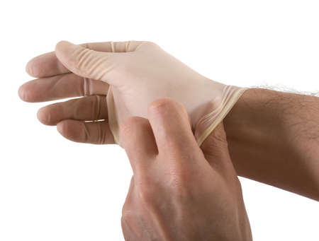 Doctor pulls on a latex glove and prepares for a medical procedure photo