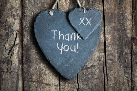 thank you note: Thank you note written in chalk on a slate heart hanging on a wooden background Stock Photo