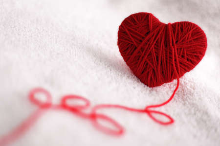 Red heart shape symbol made from wool isolated on textured white background photo
