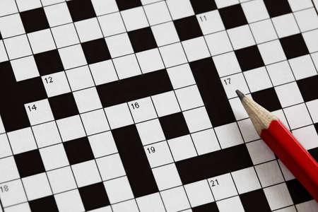 Het oplossen van een kruiswoordraadsel met rood potlood Stockfoto