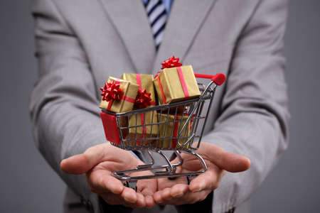 Businessman with shopping cart full of gift boxes concept for gift shopping, business gift, christmas or valentine's day gift photo