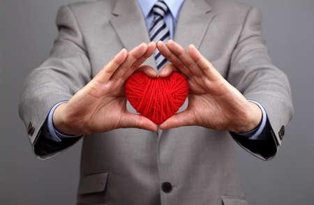 L'uomo in possesso di un concetto cuore di lana rosso per San Valentino, customer care aziendale, la carità, sociale e responsabilità d'impresa Archivio Fotografico - 24886858