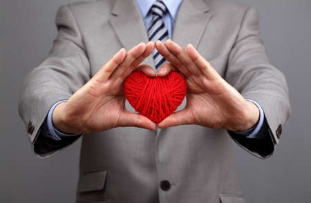 charity: Man holding a red woolen heart concept for valentines day, business customer care, charity, social and corporate responsibility Stock Photo