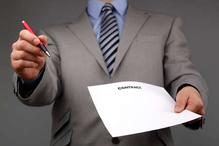 requesting: Businessmans hand holding a pen requesting a signature on a contract or document Stock Photo