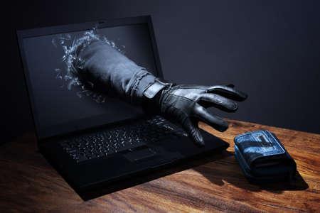 コンピュータ ハッカー、ネットワーク セキュリティ、電子バンキングのセキュリティのためラップトップ コンセプトを通じて財布を盗んだ