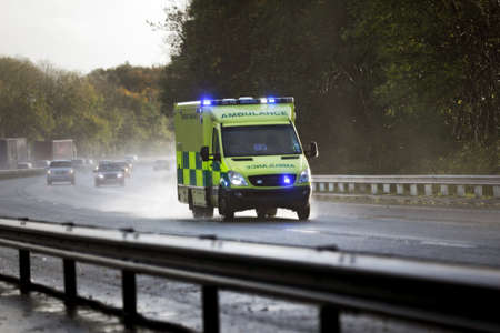 British ambulance responding to an emergency in hazardous bad weather driving conditions on a UK motorway photo