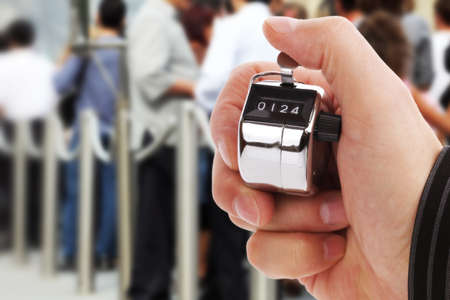 tally: Hand held tally counter counting headcount of people in a queue