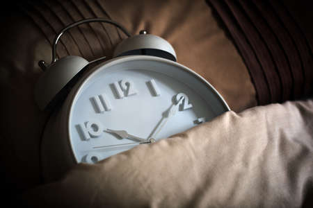 wakening: Alarm clock in bed concept for bed time, asleep, sleeping or insomnia Stock Photo