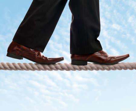 リスク、バランス、リーダーシップおよび征服の逆境のため綱渡りの概念上のビジネスマン