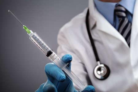 의사는 의료 주입 주사기와 청진기를 들고