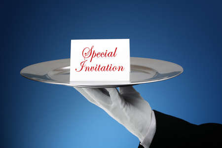 formal dinner party: Butler or waiter holding a card reading special invitation on a silver platter- message can easily be changed