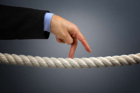 Businessmans fingers walking the tightrope concept for business risk or leadership photo