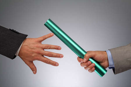 Partnership or teamwork concept two businessmen handing over a baton photo