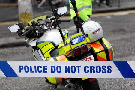 escena del crimen: Polic�a y de la motocicleta de la polic�a detr�s de la cinta del cord�n en un accidente o de la escena del crimen Foto de archivo