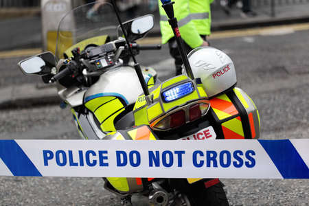 crime scene tape: Policeman and police motorcycle behind cordon tape at an accident or crime scene