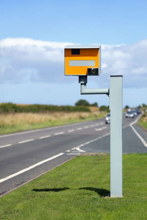 traffic ticket: UK static speed camera with speeding cars approaching on a rural road Stock Photo